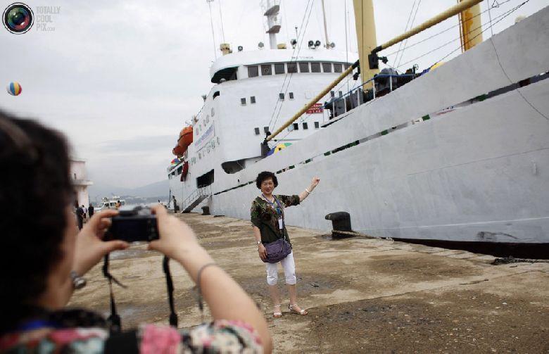 Туристка фотографируется возле круизного судна в порту Расон, который имеет статус особой экономической зоны, к северо-востоку от Пхеньяна, 30 августа 2011 года. Попытки Северной Кореи вдохнуть новую жизнь в экономические отношения с Россией и Китаем, по всей видимости, принесли свои плоды. Во вторник высокопоставленный местный чиновник сообщил журналистам, что Китай и Россия вложили значительные средства в ремонт инфраструктуры на севере страны, чтобы получить доступ к портам на восточном побережье в городах Раджин и Songbon, которые являются главными центрами северокорейской экономической зоны Расон. (REUTERS/Carlos Barria)