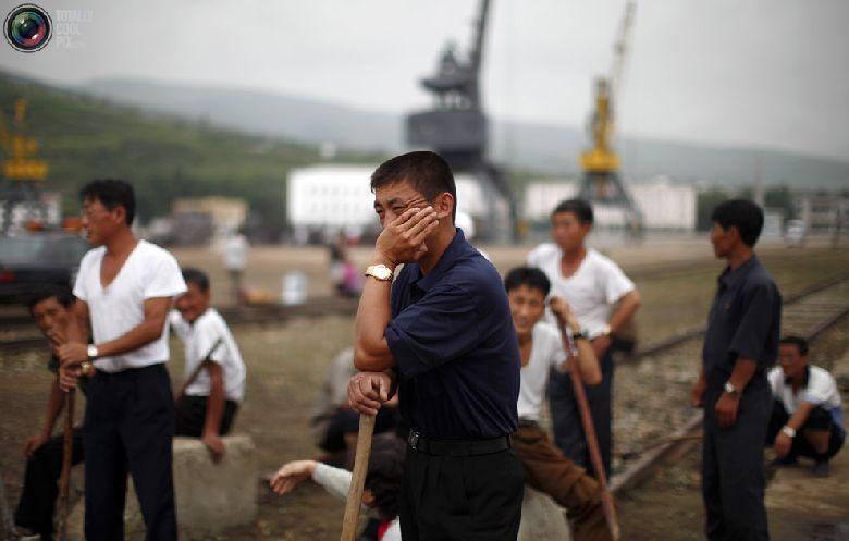 Местные рабочие отдыхают незадолго до церемонии отплытия круизного судна с туристами в порту северокорейской экономической зоны Расон к северо-востоку от Пхеньяна, 30 августа 2011 года. (REUTERS/Carlos Barria)