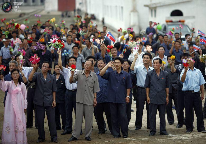 Местные жители машут круизному судну с туристами, которое покидает порт в северокорейской экономической зоне Расон к северо-востоку от Пхеньяна, 30 августа 2011 года. (REUTERS/Carlos Barria)