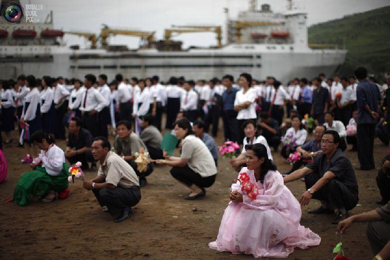 Местные жители присутствуют на церемонии отплытия круизного судна с туристами в северокорейской экономической зоне Расон к северо-востоку от Пхеньяна, 30 августа 2011 года. (REUTERS/Carlos Barria)
