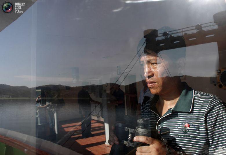 Член экипажа круизного судна смотрит на порт в курортной зоне «Гора Кымган», 31 августа 2011 года. Вокруг пустующих отелей выросла высокая трава, вьющиеся растения оплели магазины, а на дверях банка возле торгового центра висит большой амбарный замок. Это северокорейский город-призрак, который когда-то финансировался богатыми южными соседями. Опустевшая зона отдыха «Гора Кымган» раньше была символом сотрудничества между двумя Кореями, а сейчас служит суровым напоминанием о разногласиях между двумя государствами, которые фактически находятся в состоянии войны. Три года назад, когда северокорейский солдат застрелил южнокорейскую туристку, Сеул прекратил финансирование комплекса, лишив своих бедных северных соседей столь необходимого источника твердой валюты. (REUTERS/Carlos Barria)