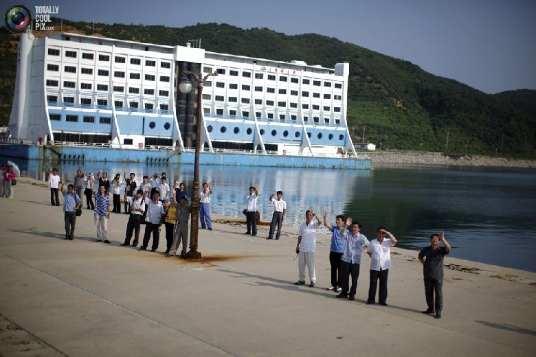 Северокорейские чиновники машут круизному судну «Mangyongbyong», которое покидает порт курортной зоны «Гора Кымган», 1 сентября 2011 года. (REUTERS/Carlos Barria)