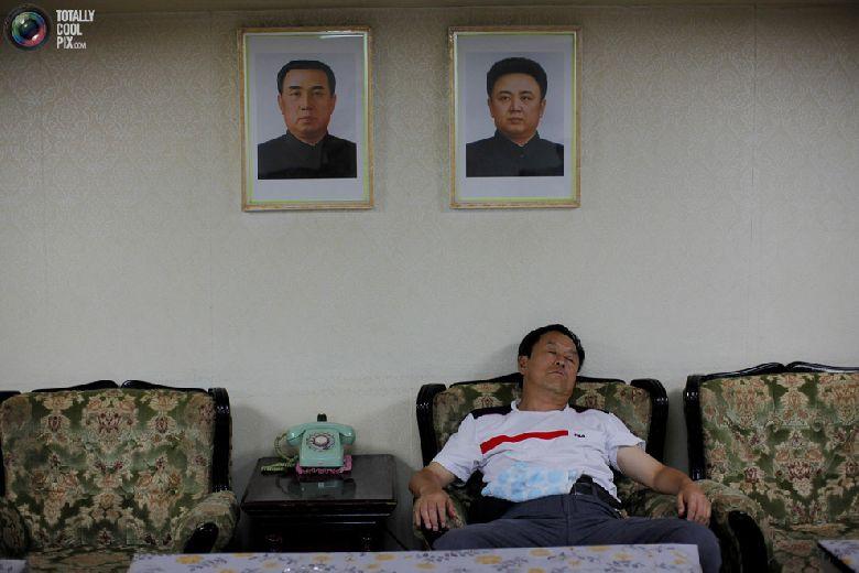 Китайский турист спит возле портретов северокорейских лидеров Ким Чен Ира (справа) и Ким Ир Сена на борту круизного судна «Mangyongbyong», совершающего свой первый рейс, 1 сентября 2011 года. (REUTERS/Carlos Barria)