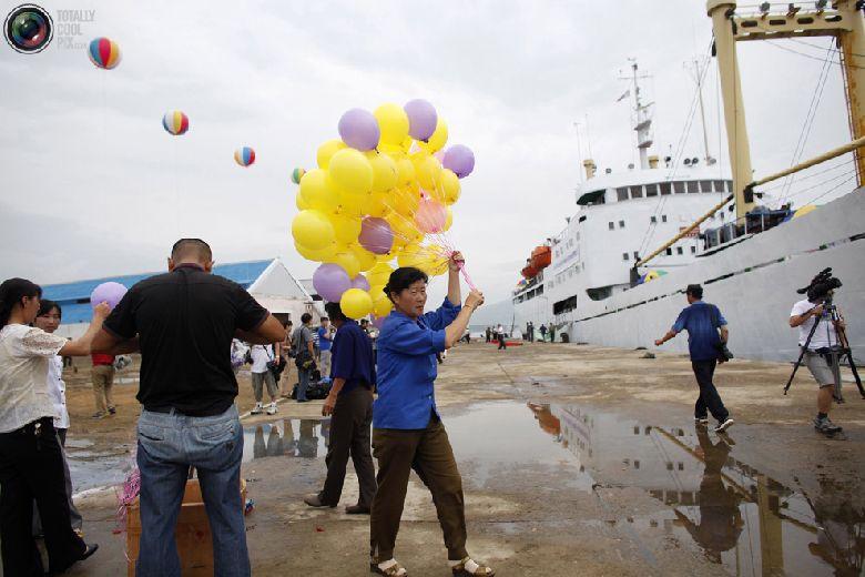 Женщина держит связку воздушных шаров перед началом церемонии отплытия круизного судна «Mangyongbyong» в северокорейской экономической зоне Расон к северо-востоку от Пхеньяна, 30 августа 2011 года. (REUTERS/Carlos Barria)