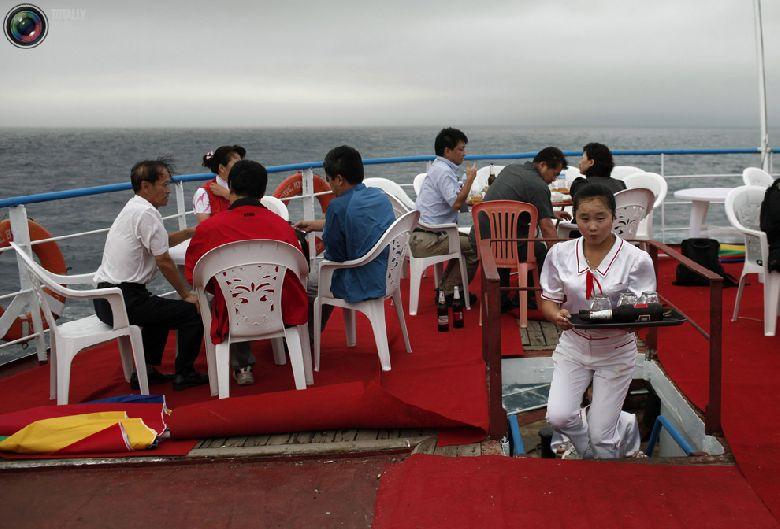 Китайские туристы сидят на палубе круизного судна «Mangyongbyong», которое совершает свой первый рейс, недалеко от северокорейской экономической зоны Расон, 30 августа 2011 года. (REUTERS/Carlos Barria)