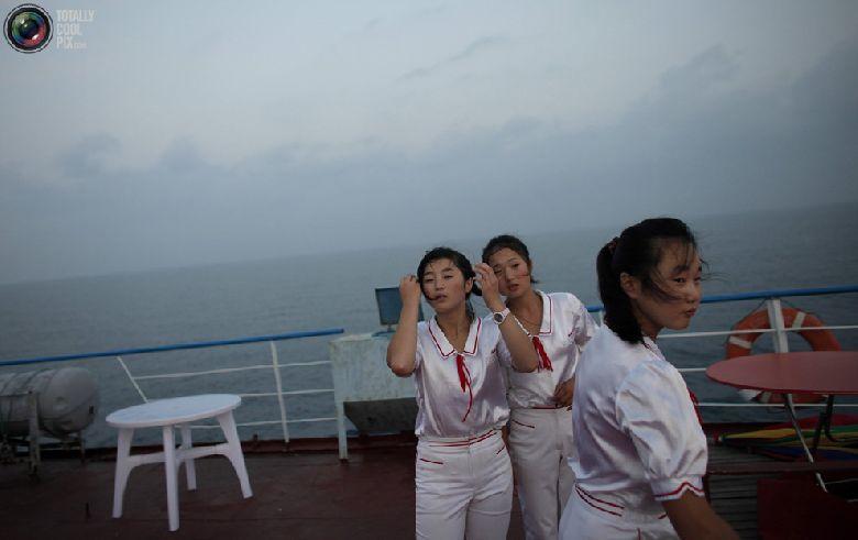 Работницы стоят на палубе круизного судна «Mangyongbyong», проплывающего мимо курортной зоны «Гора Кымган», 1 сентября 2011 года. (REUTERS/Carlos Barria)